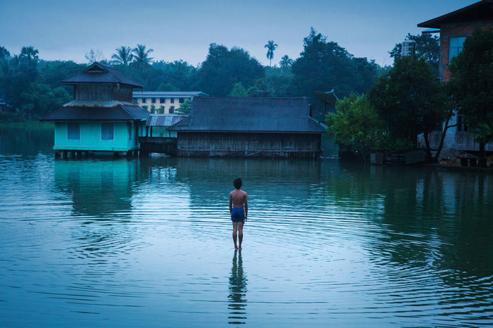 Young man standing on water in Mawlamyaing, Myanmar (2013) ;) ASIA Blue Bluehour Built Structure Dusk From Behind Lake Mawlamyaing Men Myanmar Myanmarphotos On Water One Person Outdoors People Real People Rear View Standing Stilt Stilt House Travel Travel Destinations Travel Photography Village Water
