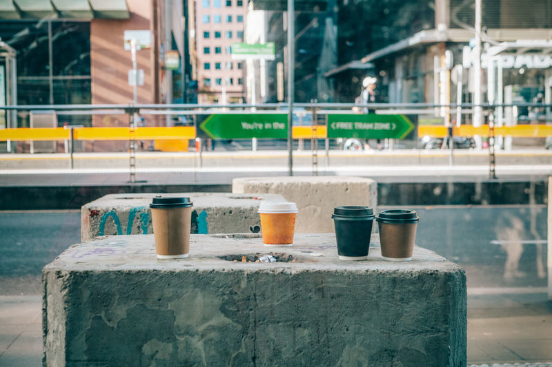 Coffee cups on concrete slab on a street in downtown Melbourne Coffee Architecture Blurred Background Building Building Exterior Built Structure City Close-up Coffee Break Coffee Cup Container Day Disposable Cup Focus On Foreground Glass Glass - Material Mode Of Transportation No People Outdoors Public Transportation Side By Side Still Life Street Street Photography Transportation Window