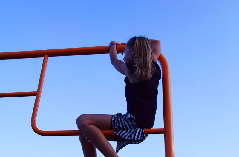 Low angle view of girl playing on railing against clear blue sky