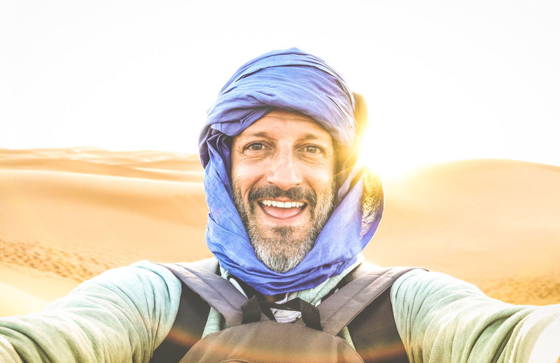 Portrait Of Smiling Man Wearing Scarf At Desert Against Sky