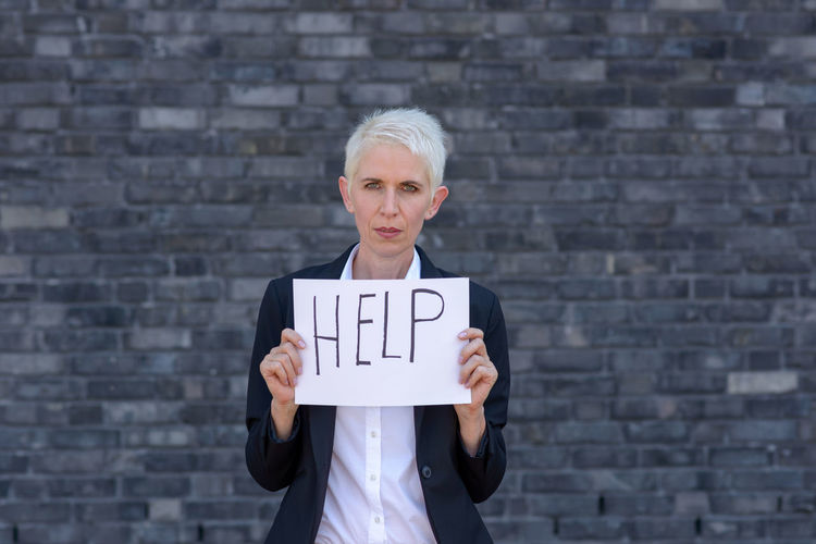Portrait of woman holding help text against brick wall