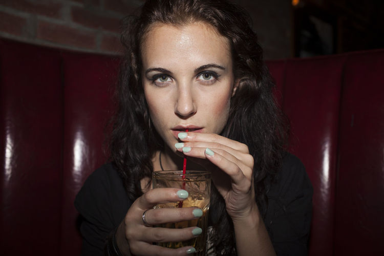 Portrait of young woman drinking glass