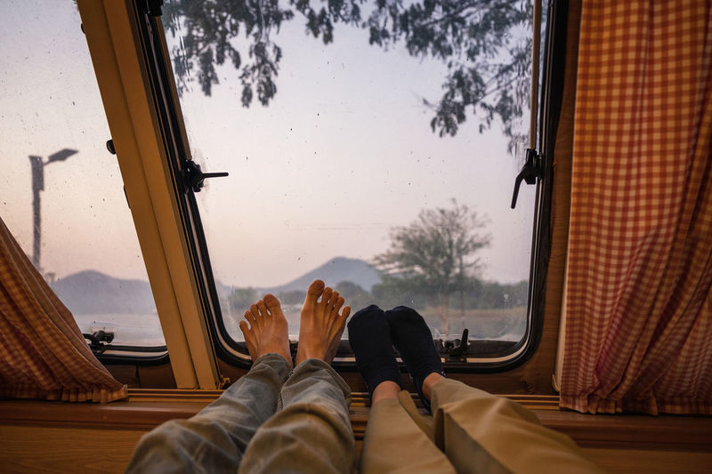 Low section of couple by window at motor home