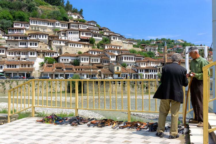 Rear view of man walking against buildings in city