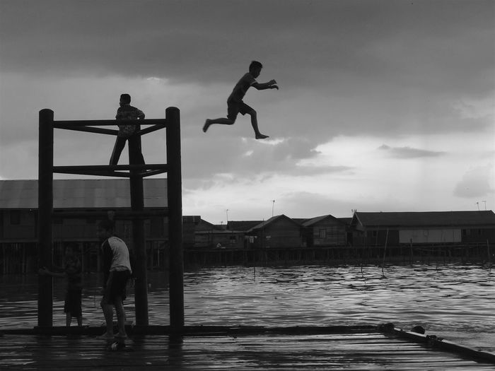 Silhouette person jumping in lake from diving platform against cloudy sky