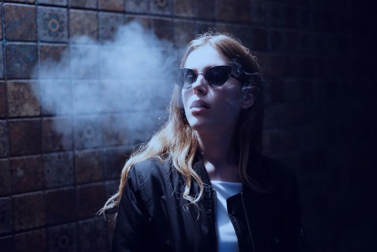 Young Woman Smoking By Wall