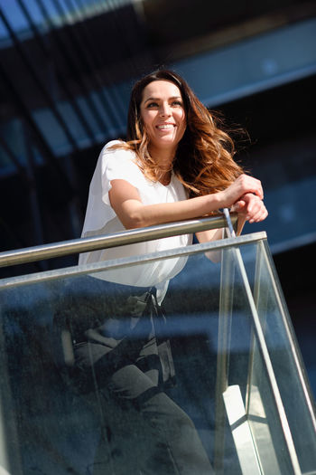 Low angle view of smiling young woman leaning on glass railing