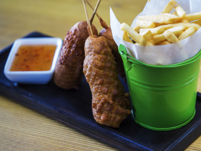 High angle view of corn dogs with french fries and spicy mayonnaise served on wooden table