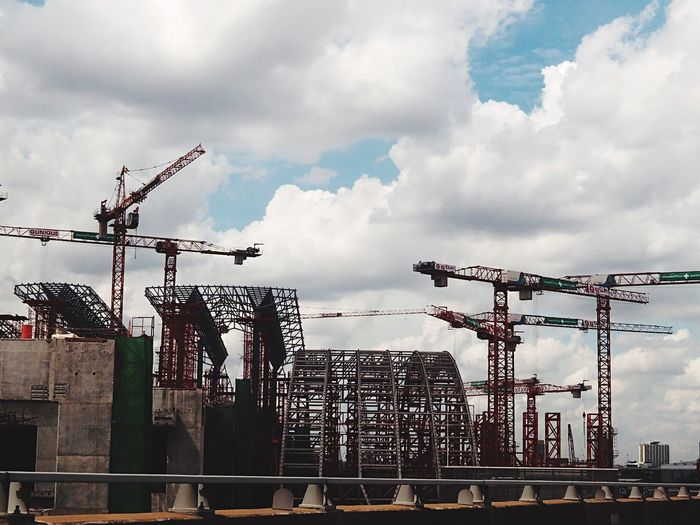 Low angle view of cranes against sky in city