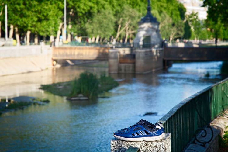 Sneakers on the edge of the river Manzanares in Madrid Architecture Bridge - Man Made Structure Building Exterior Built Structure Close-up Day Focus On Foreground Madrid Manzanares River No People Outdoors River Riverbank Sneakers Water