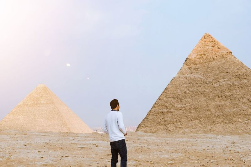 Man standing next to Giza pyramids Holiday Travel Destinations Travel Tourism Pyramid EyeEm Best Shots Middle East Skyline Egypt EyeEm Selects Architecture One Person Rear View Pyramid Sky Standing Built Structure Travel Destinations Nature Land Casual Clothing Men Desert Travel Ancient Clear Sky City Leisure Activity Ancient Civilization Outdoors 17.62° My Best Photo