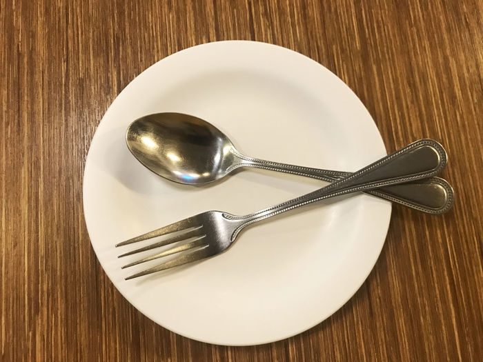 High Angle View Of Cutlery In Plate On Wooden Table