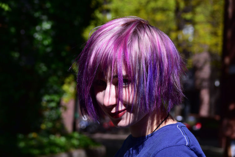 Side view of hipster woman with dyed purple hair outdoors