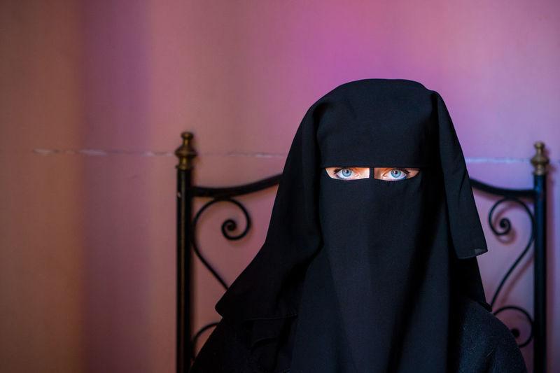 Portrait of woman wearing burka against wall