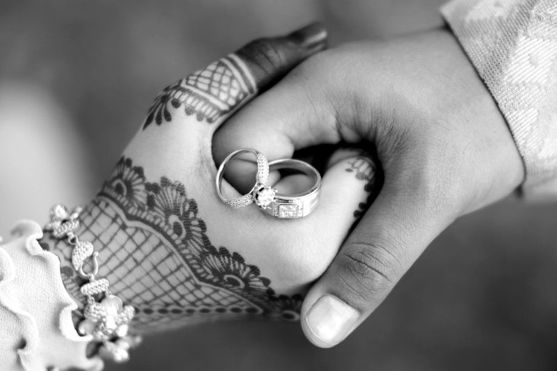 Cropped image of couple with wedding rings holding hands