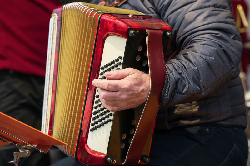 Midsection of man playing accordion