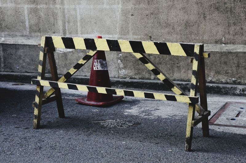High angle view of barricade with traffic cone on road against wall