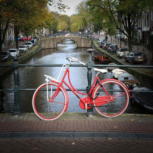Bicycle parked on bridge over canal in city