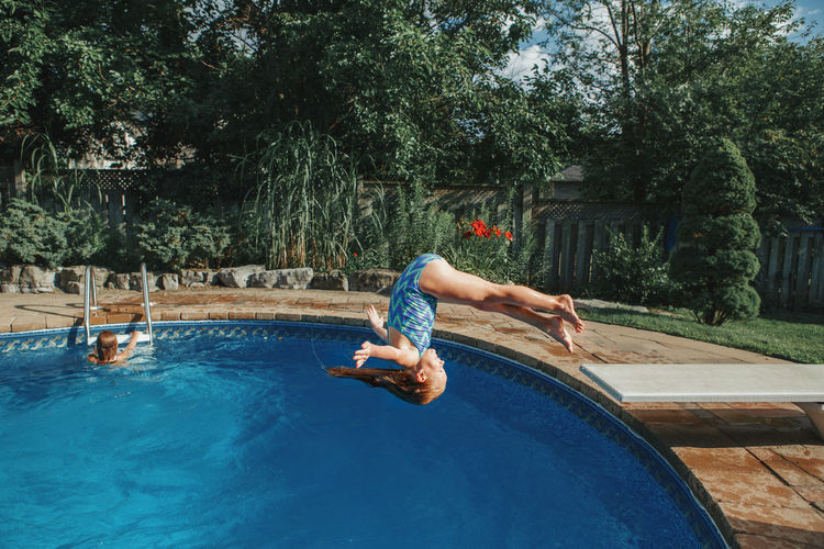 Brave athletic girl in swimsuit diving in pool from springboard. child having fun in swimming pool