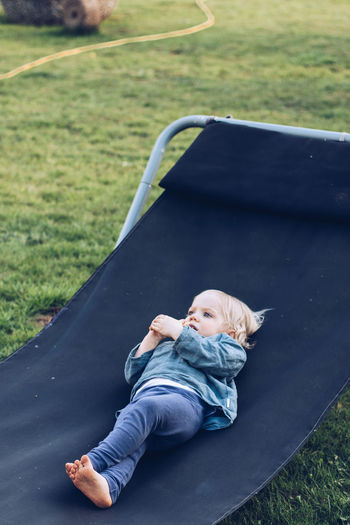 Full length of baby girl relaxing on folding chair at lawn