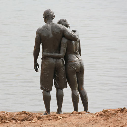 Rear view of muddy couple at beach