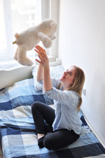 Bed Blonde Casual Clothing Cute Girl Happiness Happy Home Lifestyles Light Person Pillow Relaxation Sitting Sofa Sun Light Teddy Teddybear White