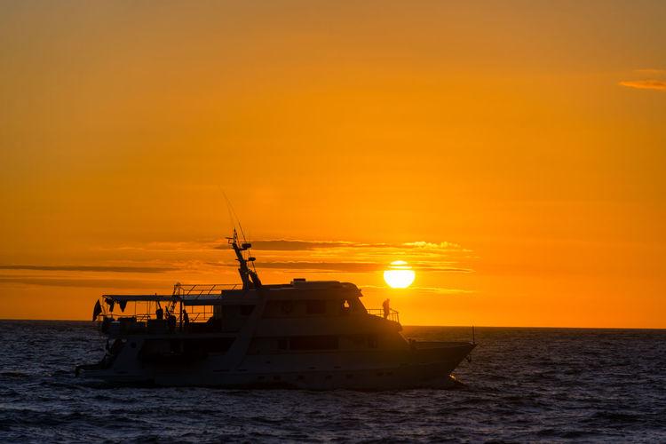 Boat Sailing On Sea Against Orange Sky