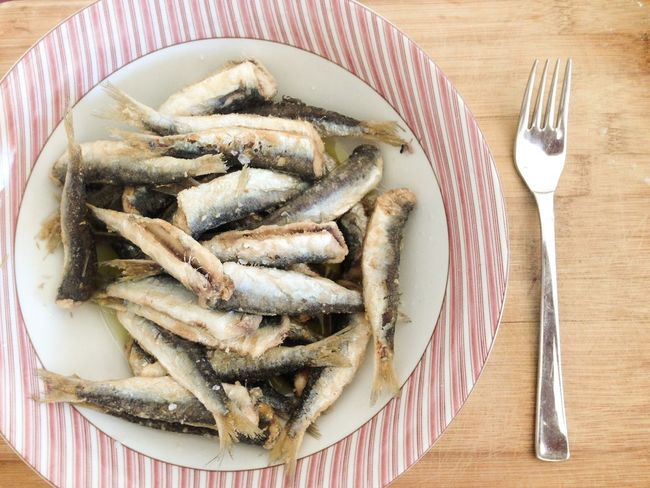 Roasted sardines fish on plate on wooden board Above Anchovies Dinner Food Food And Drink Fork Gourmet Healthy Eating Indoors  Lunch Meal Mediterranean  Olive Oil Plate Sardine Sardines Seafood Table Tasty Top View Wooden Board