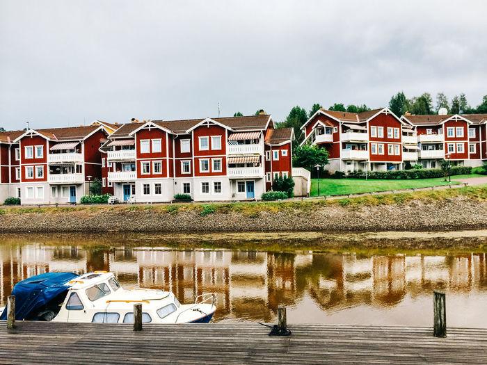 Boat Moored At Lake Against Buildings