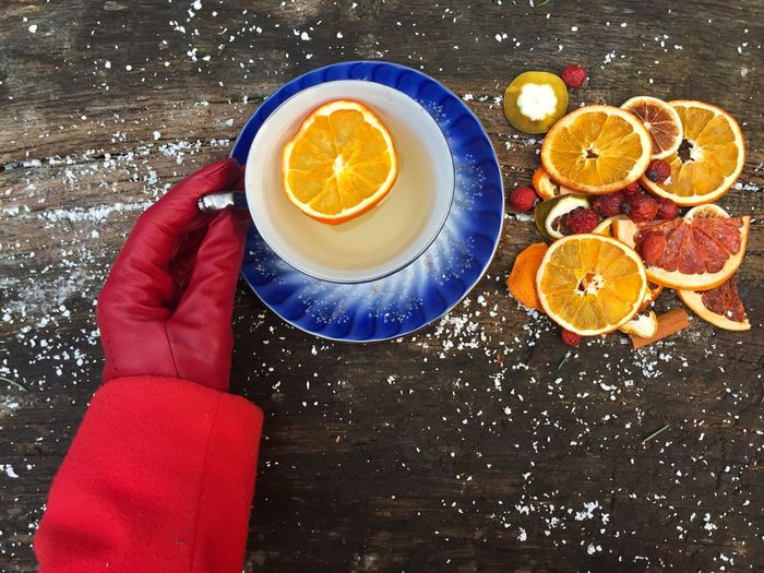 View of gloved hand with orange tea on table