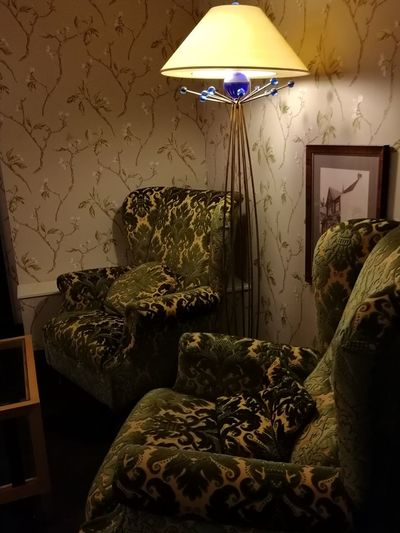 Close-up of illuminated electric lamp on sofa at home