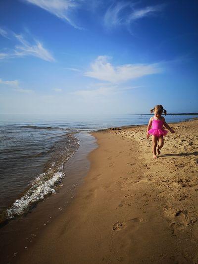 Girl walking on shore at beach against sky