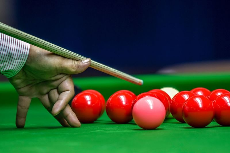Cropped hand of man playing snooker