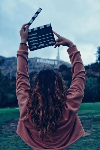 Rear view of woman with arms raised holding film slate against sky