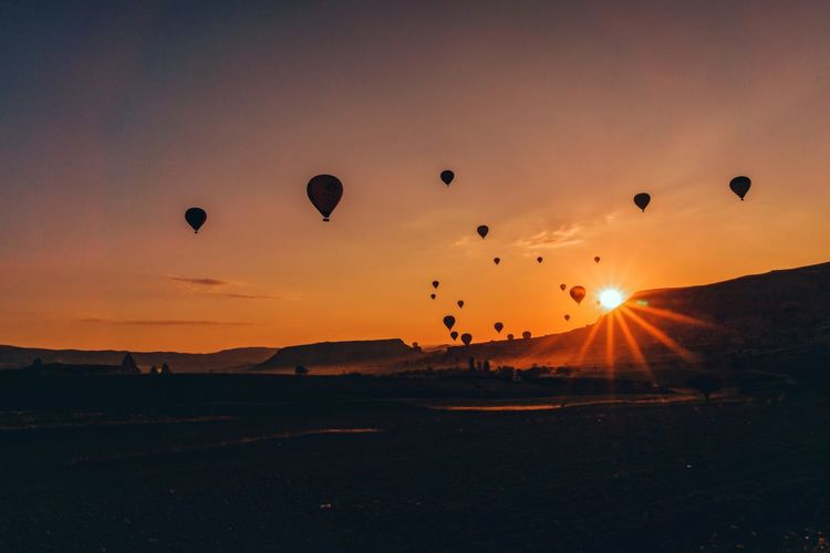 Hot air balloons flying over land during sunset