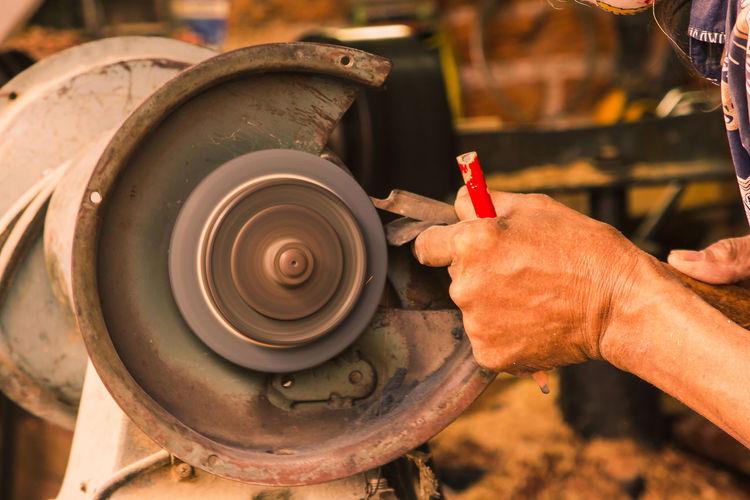 Midsection of man sharpening metal on grinder