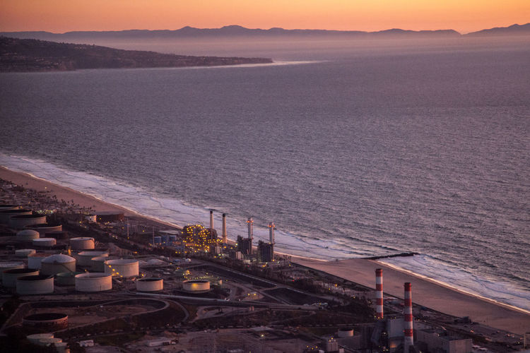High angle view of industrial buildings by sea during sunset