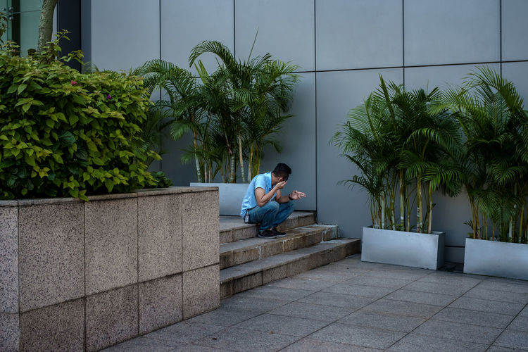 Side view of boy sitting on plant against building