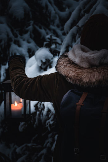 Person carrying lantern in dark winterly forest