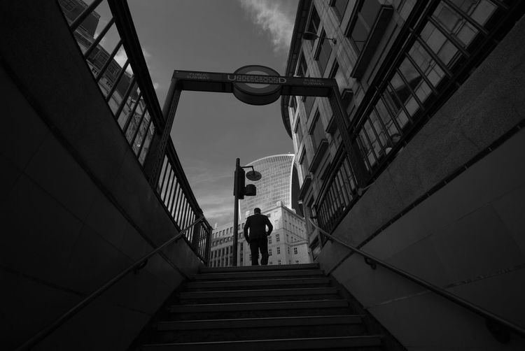 Low Angle View Of Man Walking On Staircase In City