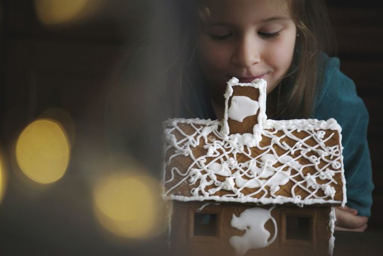 Close-up of girl with gingerbread house on table
