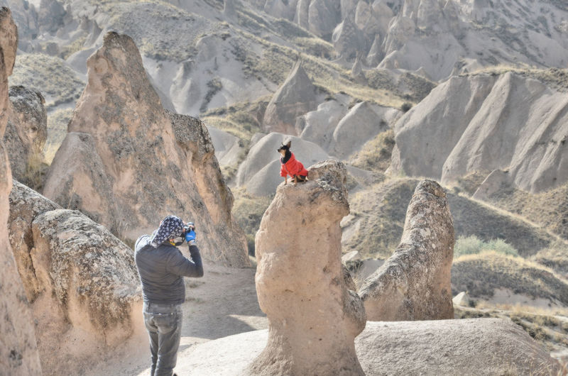 Man photographing dog on rock formation