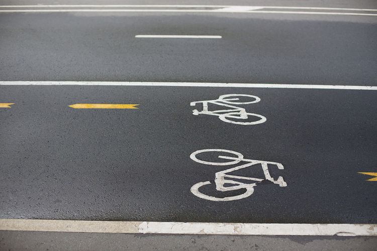 Sign of bicycle lane on wet asphalt Street Urban Lane Sign Symbol Asphalt Cycle Transportation Scene Bicycle Road Transport Lifestyle Safety City Empty Footpath Park Mark White Pursuit  Travel Ride Recreational  Traffic Location Curve Paint Exercising Healthy Amusement  Direction Outdoors Environment Ground Simplicity Sport Arrow Road Marking Marking Communication High Angle View No People Bicycle Lane Guidance White Color Day Architecture