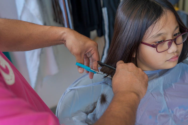 Asian young girl wearing glasses getting haircut at home from the father.