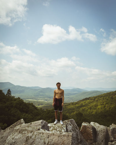 Shirtless man standing on rock against mountains