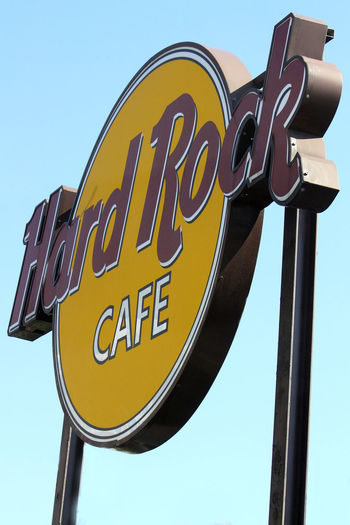 Hard Rock Cafe Sign Clear Sky Close-up Communication Day Low Angle View Metal No People Outdoors Popular Restaurants Around The World Restaurant Signs Sky Text Western Script Yellow Postcode Postcards