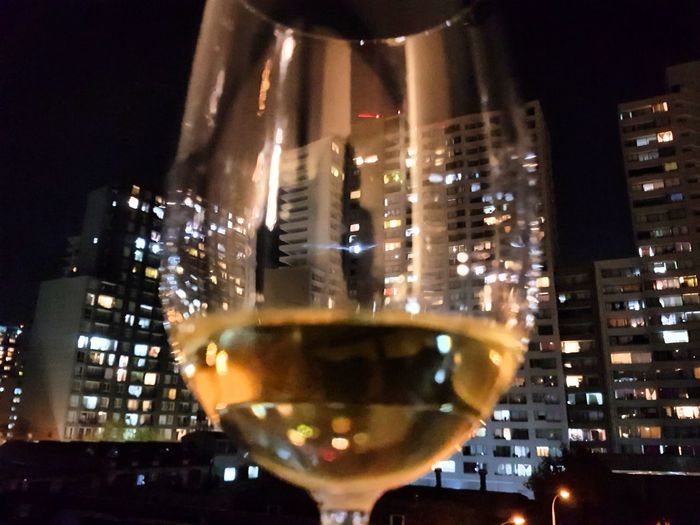 Close-up of wine in illuminated city at night