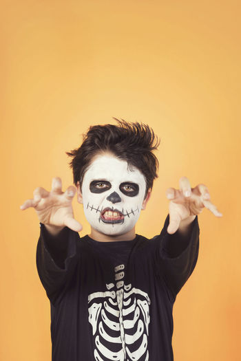 Portrait of boy in costume with face paint gesturing against orange background