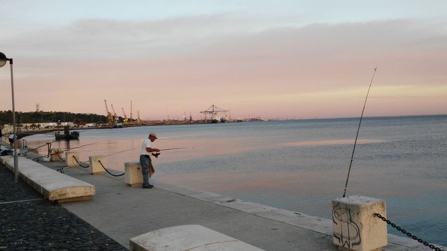 Man fishing at harbor against sky during sunset