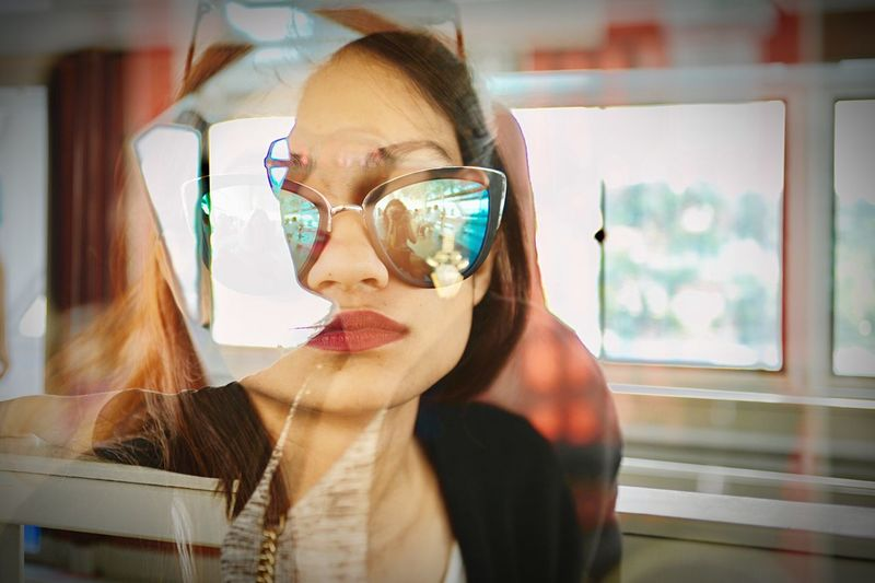 Double exposure image of woman wearing sunglasses at home